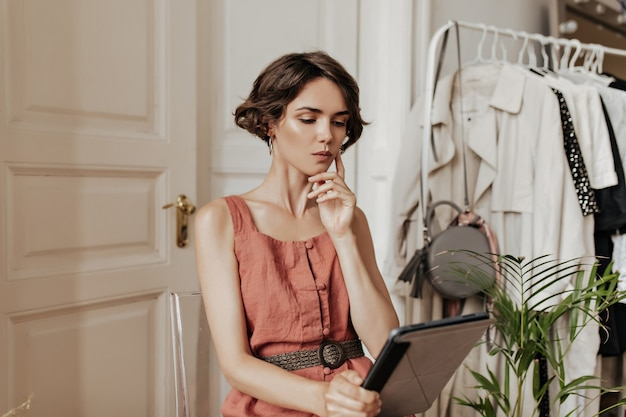 Thoughtful short-haired young woman in linen red dress sits on chair in cozy light room and holds computer table