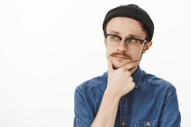 Thoughtful smart and creative handsome stylish guy with beard and moustache in black beanie and glasses gazing left with focused expression rubbin chin, thinking considering agree on deal