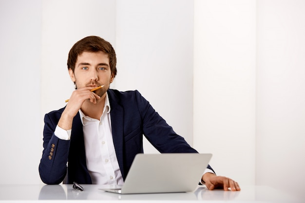 Thoughtful smart man in suit sit at his office with laptop, touch lip as pondering, taking important decision