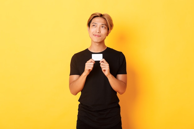 Задумчивый улыбающийся азиатский парень думает, показывая кредитную карту, мечтательно смотрит в левом верхнем углу, желтая стена