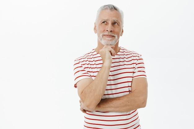 Задумчивый улыбающийся пожилой мужчина смотрит в левый верхний угол с довольным лицом