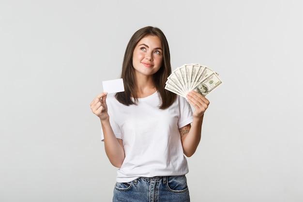 お金とクレジットカードを持って、左上隅を見て、白く立って熟考している思いやりのある笑顔の女の子。