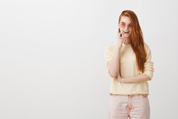 Задумчивая улыбающаяся рыжая девушка кусает палец и выглядит заинтригованной, у нее есть интересная идея