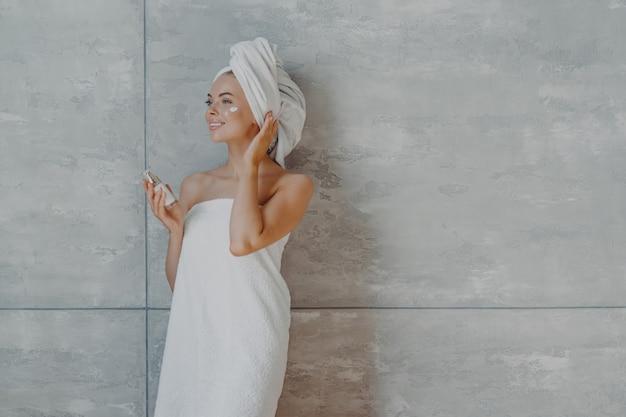 Задумчивая улыбающаяся молодая женщина наносит на лицо тональный крем или увлажняющий крем
