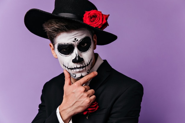 할로윈 정장을 입고 포즈를 취하는 심각한 표정으로 챙이 넓은 검은 모자에 사려 깊은 스페인 남자.