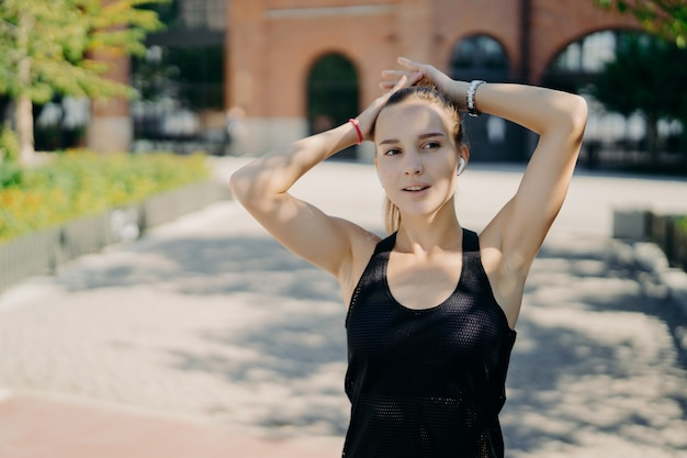 Thoughtful sporty woman concentrated into distance breathes deeply after jogging takes break during cardio training dressed in black t shirt keeps hands on head listens audio track in earphone