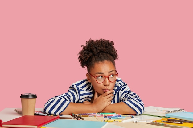 ピンクの壁に向かって机でポーズをとる思いやりのある学生の女の子
