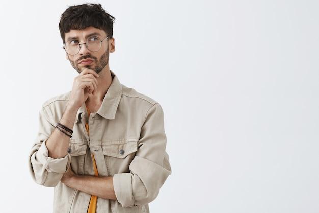 Вдумчивый стильный бородатый парень позирует у белой стены в очках