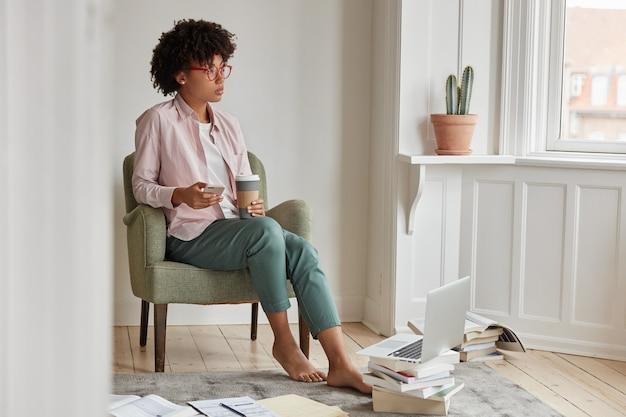 Premuroso startupper femminile di successo gode di una bevanda al cappuccino, tiene una tazza da asporto, si siede in poltrona, utilizza il telefono cellulare e il computer portatile