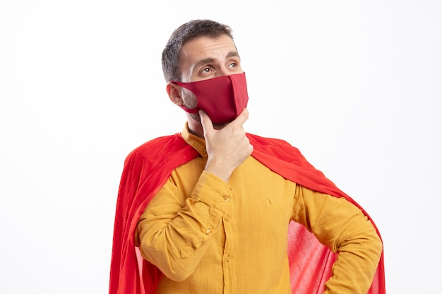 Thoughtful superhero man with red cloak wearing red mask puts hand on chin and looks at side isolated on white wall
