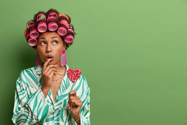 La ragazza delle caramelle premurosa e sorpresa guarda sopra, posa con un delizioso lecca-lecca, indossa bigodini per fare bigodini perfetti, indossa il pigiama, sta contro il muro verde, uno spazio vuoto a destra