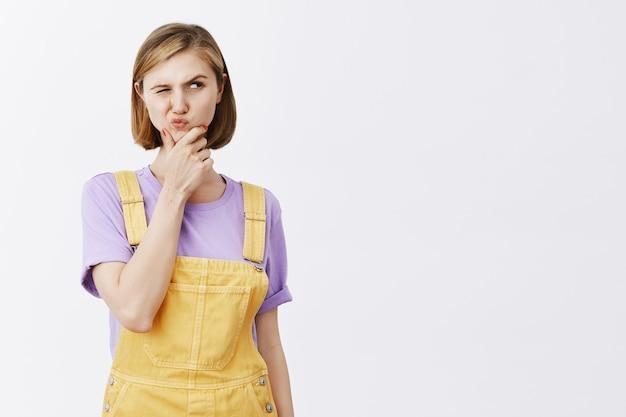 Задумчивая подозрительная молодая женщина хмурится и смотрит прямо, любопытно, думает, принимает решение