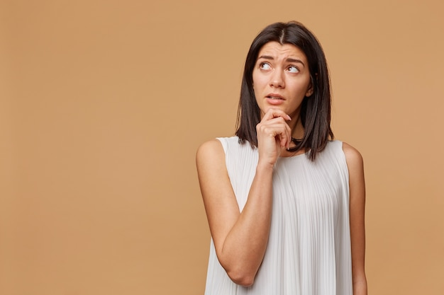 Thoughtful tanned woman standing hand holding chin looking at the upper left corner at the blank copyspace with a little caution, portrays the excitement,