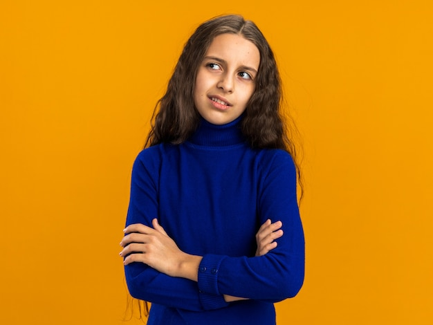 Thoughtful teenage girl standing with closed posture looking at side isolated on orange wall with copy space