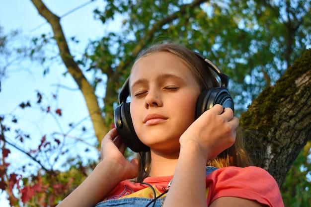음악 야외 음악을 듣고 헤드폰에 사려 깊은 십 대 소녀.