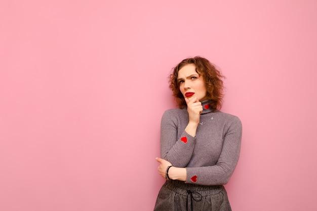 Задумчивая девочка-подросток с вьющимися рыжими волосами и в сером свитере