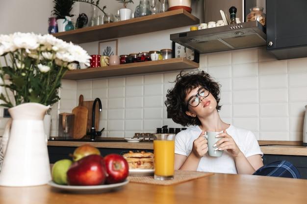 お茶を飲みながらキッチンに座っている思慮深い思考かなり巻き毛の女性