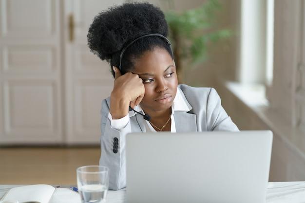 思いやりのある疲れたアフロの実業家は、オフィスでラップトップで働いて、窓を見ながらヘッドフォンを着用します。