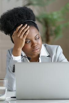思いやりのある疲れたアフロの実業家は、窓を見て、ラップトップで働いて、クローズアップでヘッドフォンを着用します。