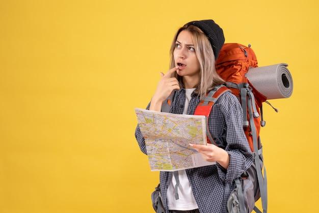 Donna viaggiatrice premurosa con lo zaino che tiene mappa