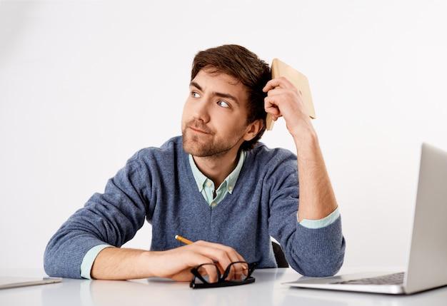 Вдумчивый, беспокойный молодой офисный работник, не хватает идей, отводит взгляд с надутым серьезным лицом, пробует придумать идеи для новой истории, держит планировщик и карандаш