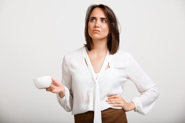 Donna di moda sconvolto pensieroso bere caffè, pensando