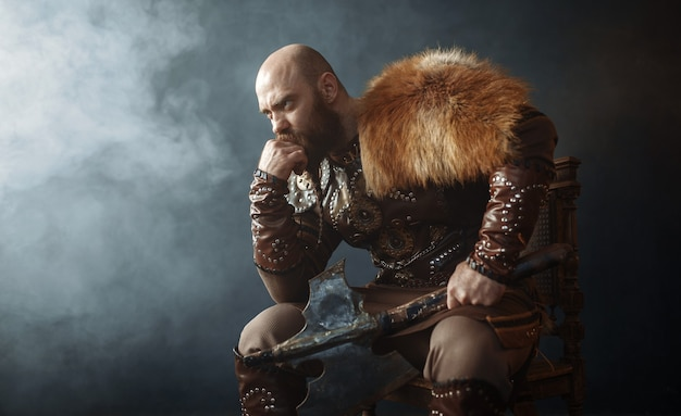 Thoughtful viking with axe dressed in traditional nordic clothes sitting on chair, barbarian image. ancient warrior in smoke