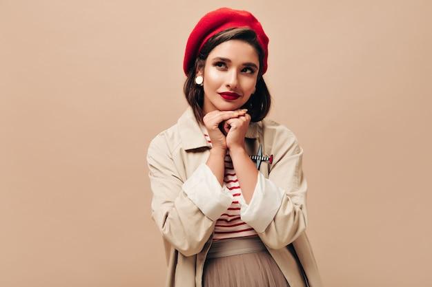 Premurosa donna in trincea beige e cappello pone su sfondo isolato. la bella ragazza sveglia in maglione e mantello a strisce osserva in su.