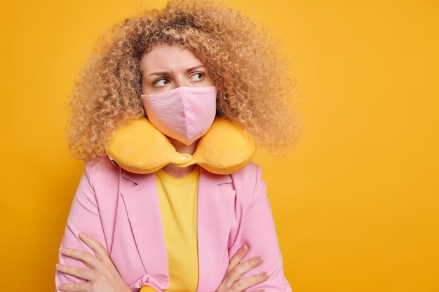 La donna premurosa che si autoisola indossa una maschera protettiva contro il coronavirus indossa un cuscino per il collo tiene le braccia conserte contempla qualcosa di isolato sul muro giallo con uno spazio vuoto