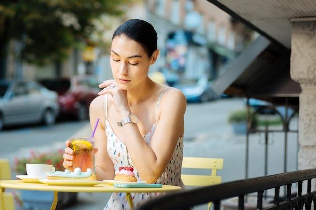 思いやりのある女性。ストリートカフェを訪れ、レモネードをじっくりと見つめる穏やかな若い女性