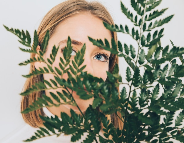 Thoughtful woman covering face with fern leaves