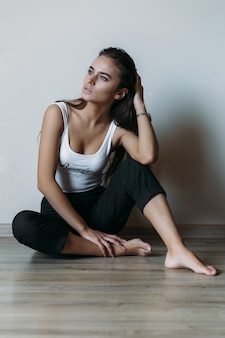 Thoughtful woman dressed in casual style sits on the floor in an empty room