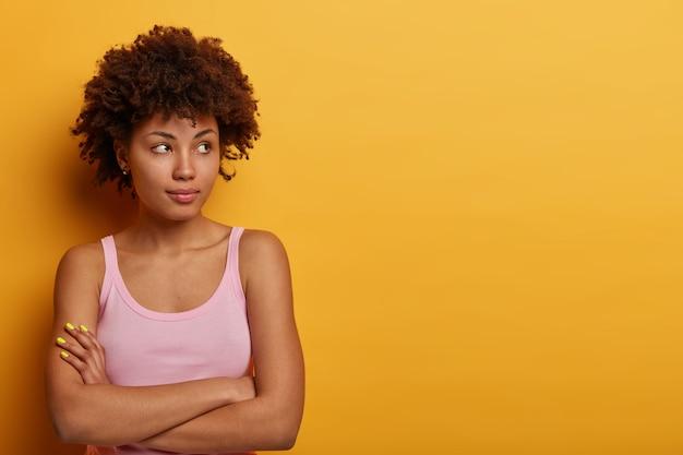 사려 깊은 여자는 건강한 피부, 자연스러운 곱슬 머리를 가지고 있으며 팔을 접고 옆으로 쳐다 보며 캐주얼 한 옷을 입고 노란색 벽에 고립되어 결정을 시도합니다.