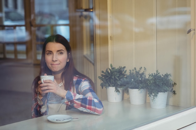 Thoughtful woman having coffee at cafe