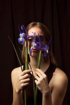 Thoughtful woman holding blue flowers at face