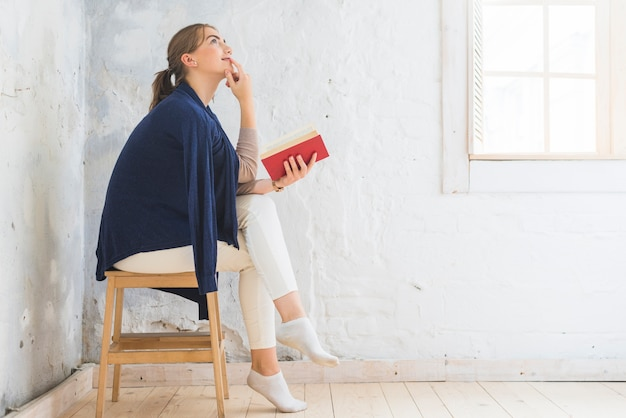 Thoughtful woman holding book sitting on stool