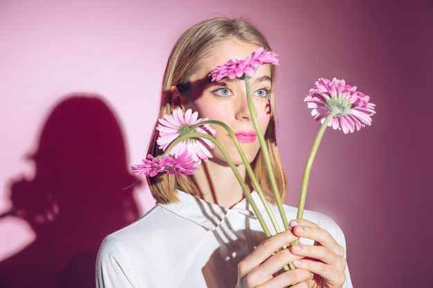 Thoughtful woman holding pink gerbera flowers
