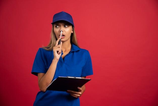 クリップボードと鉛筆でポーズをとる青い制服を着た思いやりのある女性。