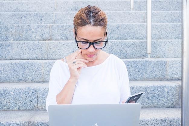 屋外の階段に座って携帯電話を保持し、ラップトップを使用して眼鏡をかけた思いやりのある女性。市内の石の階段に座ってラップトップを使用して忙しい実業家