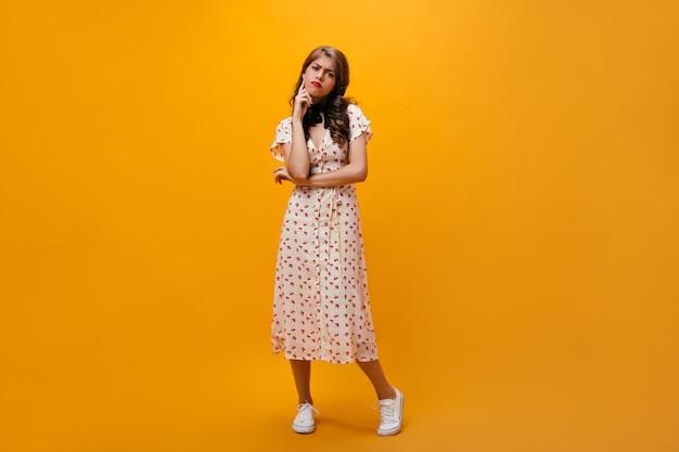 ミディドレスの思いやりのある女性はオレンジ色の背景にポーズします。クールなファッショナブルな服とスニーカーで巻き毛の髪型の悲しい女の子がカメラをのぞきます。