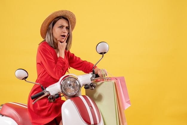 쇼핑 가방을 들고 오토바이에 빨간 드레스에 사려 깊은 여자