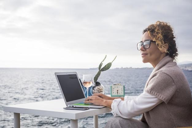 Задумчивая женщина в свитере и очках работает на своем ноутбуке на открытом воздухе