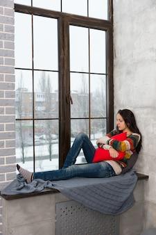 枕を抱き締めて窓の外を見ながら窓辺に横になっている暖かいニットのセーターを着た思いやりのある女性