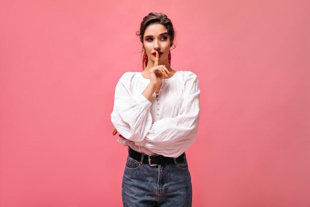 ピンクの背景に白いブラウスの思いやりのある女性のポーズ。幅の広いベルトのジーンズで黒髪の赤い口紅のかわいい女の子が横に見えます。