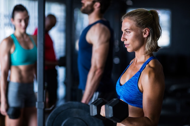 Thoughtful woman lifting dumbbell in gym