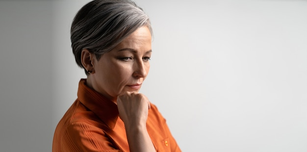 Thoughtful woman looks away touching chin with hand