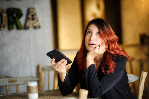 Задумчивая женщина смотрит вверх, держа свой мобильный телефон