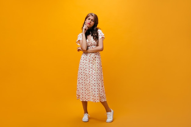 Thoughtful woman in midi dress poses on orange background.sad girl with curly hairstyle in cool fashionable clothes and sneakers looking into camera.