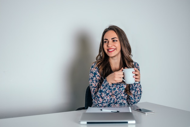 Thoughtful woman in office drinking coffee.