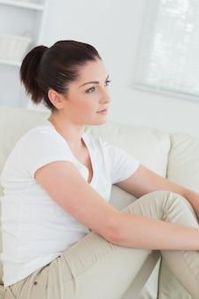 Задумчивая женщина на диване